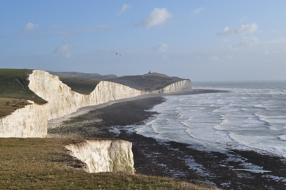 A distant view of Beechyhead Lighthouse and the Seven Sisters, a line of cliffs, stretching eastwards.