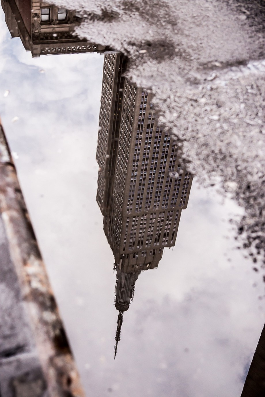 The Empire State Building reflected in a pool of melted snow. by MikaJC - New York Photo Contest