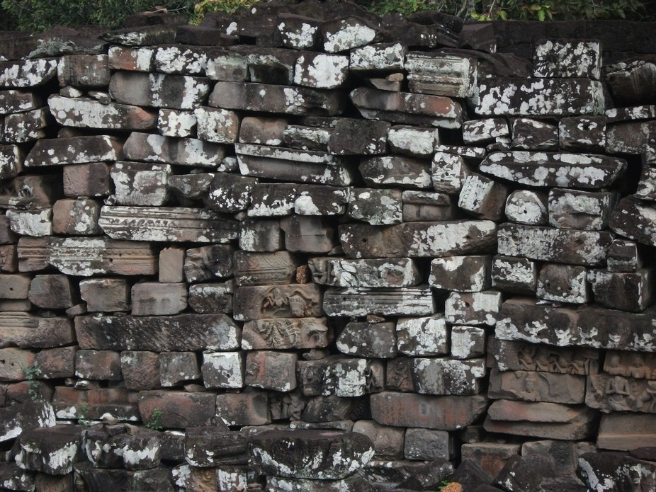 One of many stone walls in the surrounding areas of a Cambodian temple.