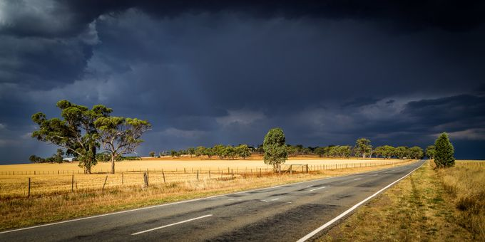 Dark Clouds over a Sundrenched Road by travisdaldy - A Road Trip Photo Contest