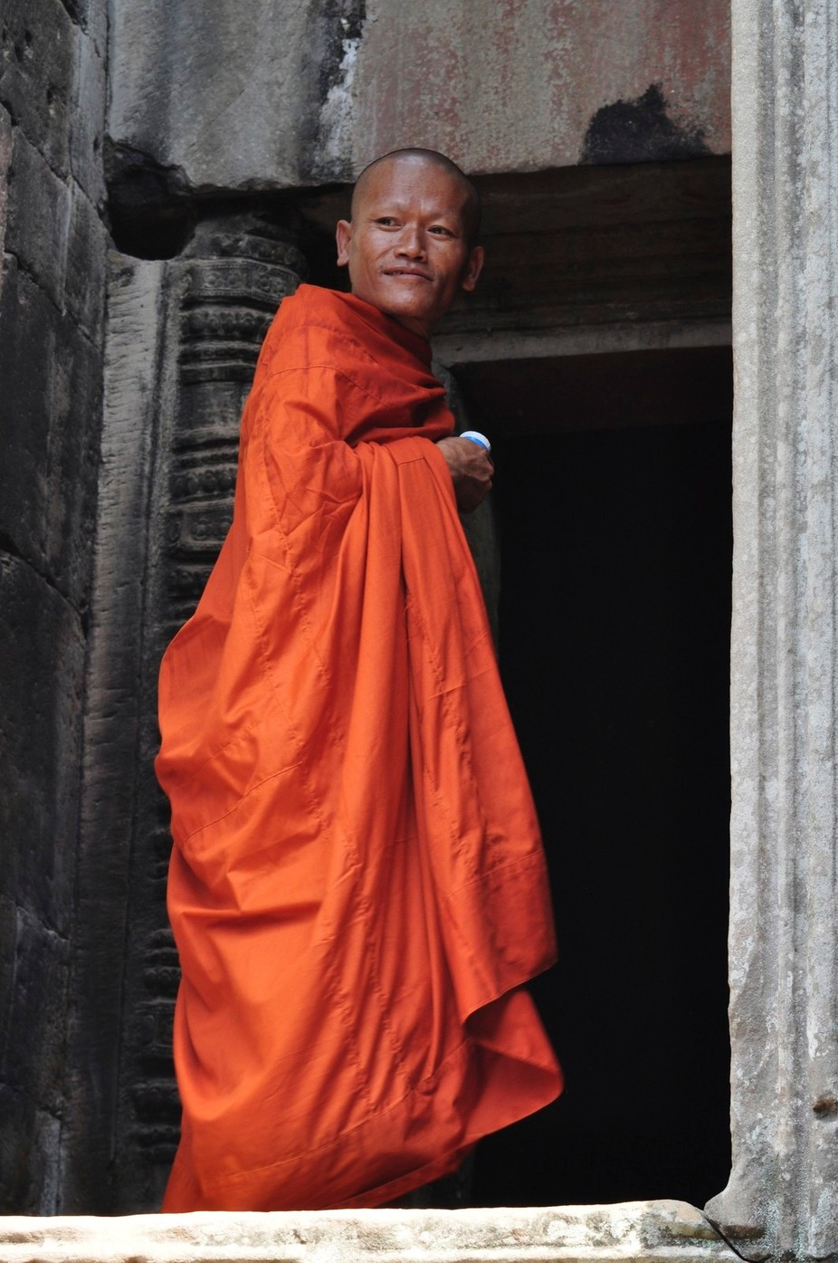 A young Buddhist monk at Angkhor Wat observes the foreign visitors