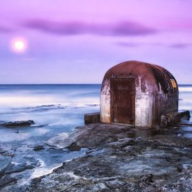 Full moon rising over the ocean as the final colours of sunset bath the old pump house in hues of pink and purple.
