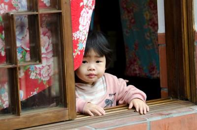 Little Girl looking out window in Chiayi Taiwan