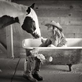 Cowgirl in clawfoot bath tub speaks to her horse and comforts him from the clawfoot tub in the barn