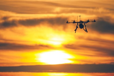 A silhouette of a flying Drone at sunset
