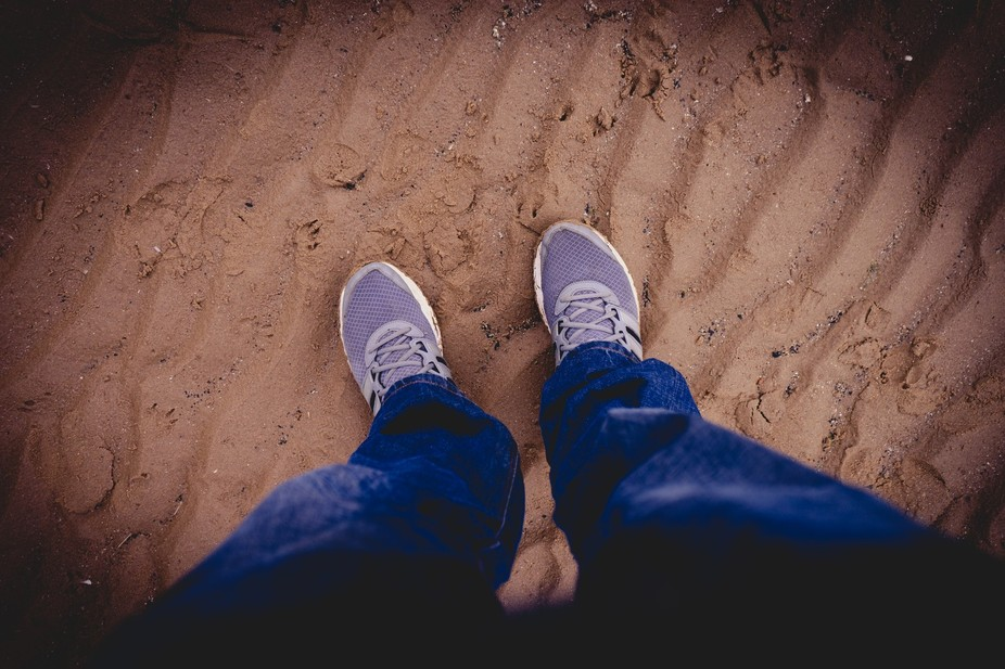 Looking down at shoes on a beach