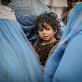 A young child sits amidst several women wearing blue burqas at a food distribution in the Afghan capital.