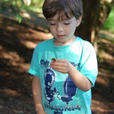 LITTLE BOY INSPECTING CATERPILLAR on his finger, on HORNE LAKE, VANCOUVER ISLAND - BRITISH COLUMBIA, CANADA - June 2015