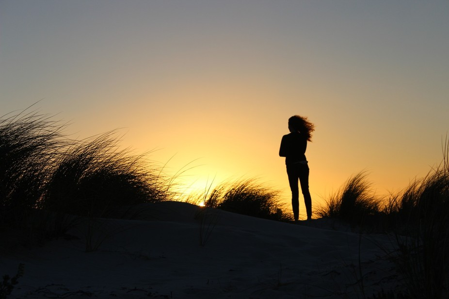 As my wife climbed to the top of this dune near Cape Town the wind and sun-set caught her hair in...