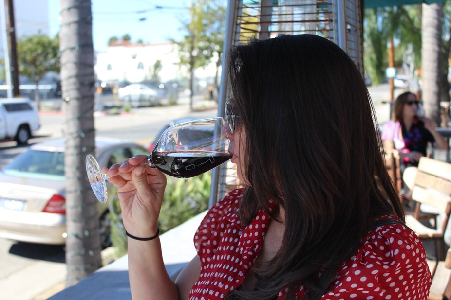 A woman sipping on a glass of red wine
