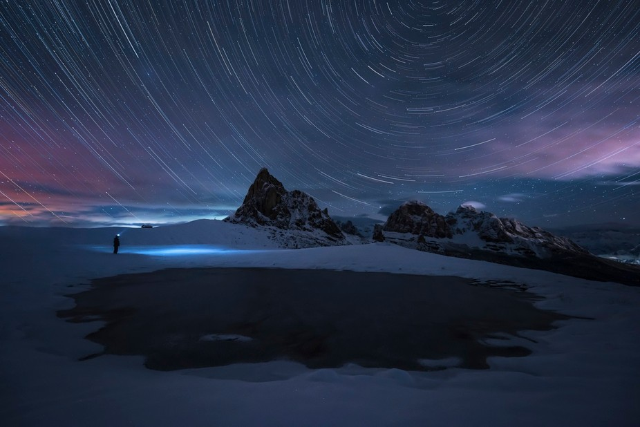 Taken with the first winter snowfall on the Passo Giau in the Italian Dolomites. The small lake at the top of the pass had just frozen creating a beautiful site from which to view the stars.