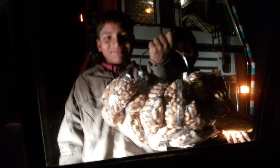 In the approaching car's light the boy selling groundnuts at night.....