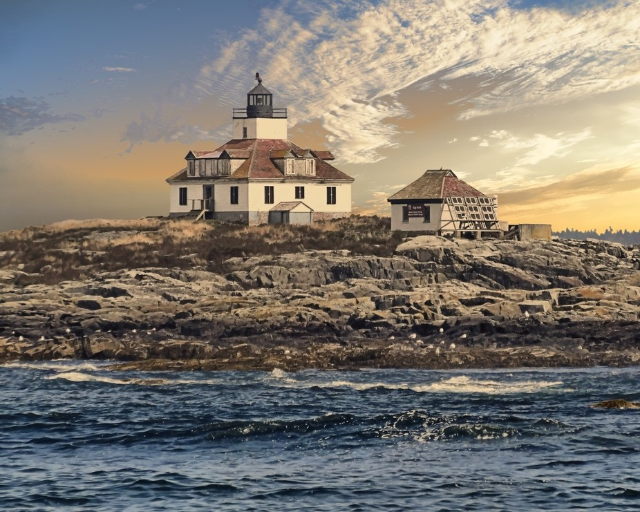 An isolated lighthouse sits on a small island of land off the Maine coast.