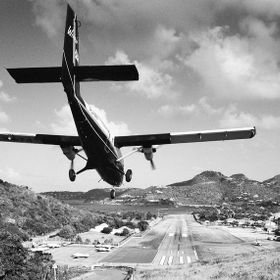 The airplane has to land on a very short runway. So the pilot has to fly very spectacular between two mountains over a roundabout on the ridge to...