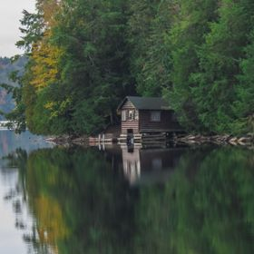 A small cottage hidden in a small cove on a Northern Lake sits in the stillness of the morning.