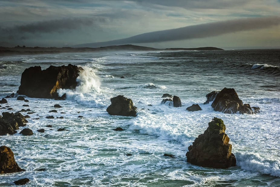 Under grey skies, powerful waves crash against the rocks in Mendocino County, California. On the ...
