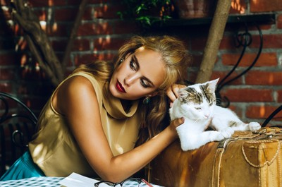 Portrait of a beautiful blonde girl holding cat