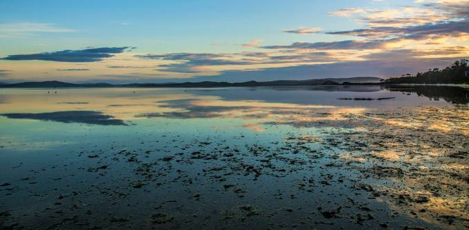Low tide and the wet mud flats reflect the colorful sunrise at Simpsons Bay, Bruny Island, Tasmania.