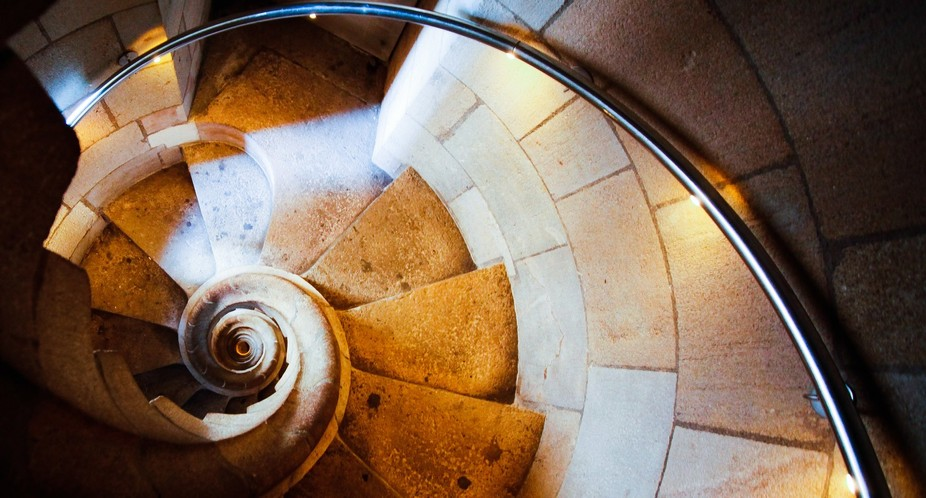 A view down a spiralling staircase in one of the towers of the Sagrada Familia by Architect Anton...