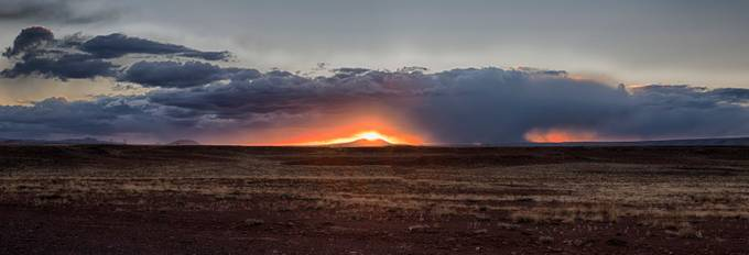 Taken as we drove south from the eastern edge of the Grand Canyon.   I noticed the sun was setting directly over the mountain.  This is a pano of several raw photographs, merged with AutoPano.