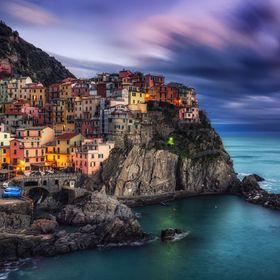 beautiful sunset over manarola in cinque terre, Italy. Sunlight lighting up the tips of the stormy clouds just before the night dawned. Manarola ...