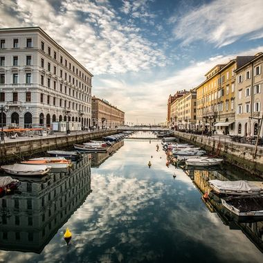 Amazing clouds reflecting in the still Grand Canal of Trieste, Italy
