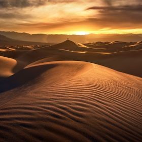 The Mesquite Dunes of Death Valley NP at sunset. Endless sand formations carved by the wind. Giant dunes in the distance with the occasional clim...