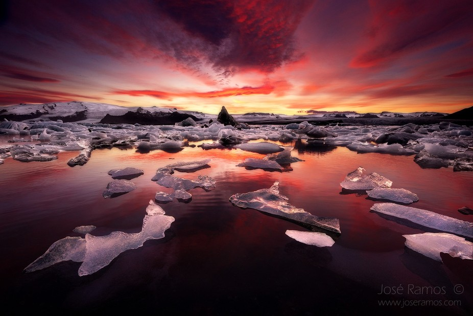 The Jokulsarlon Glacier Lagoon under fiery light, in it's endless cadence of moving piec...