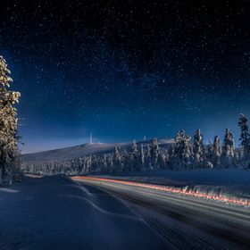 Light trails of a car passing by on the Ylläs Scenic Road in Lapland, Finland