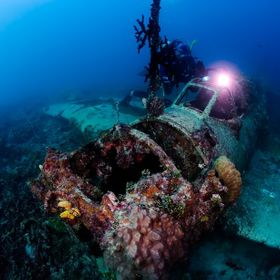 "Scuba diver exploring wrecked  airplane. This airplane called ""Zero"" was sunken 70 years ago during Second World War."