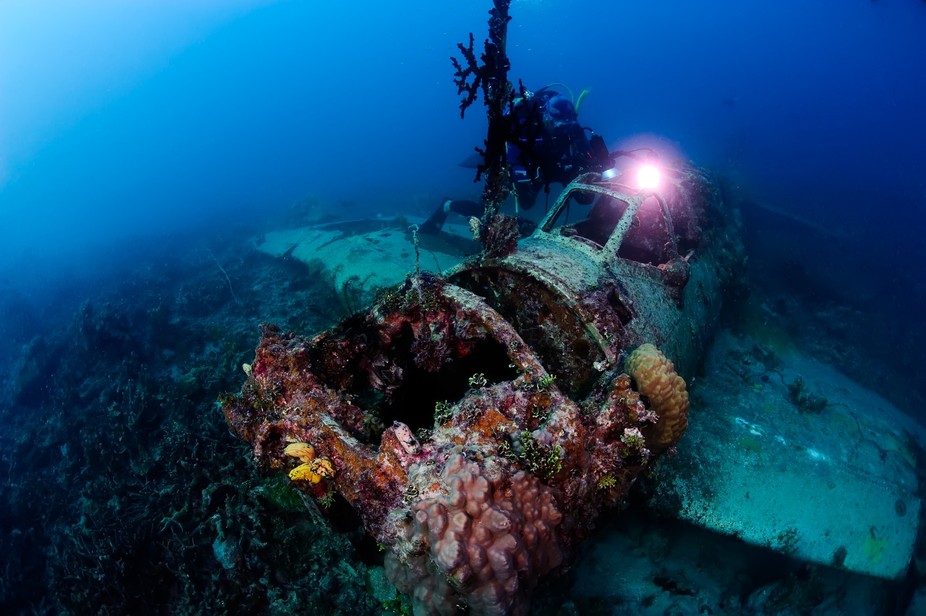 "Scuba diver exploring wrecked  airplane. This airplane called ""Zero"" was sunken..."