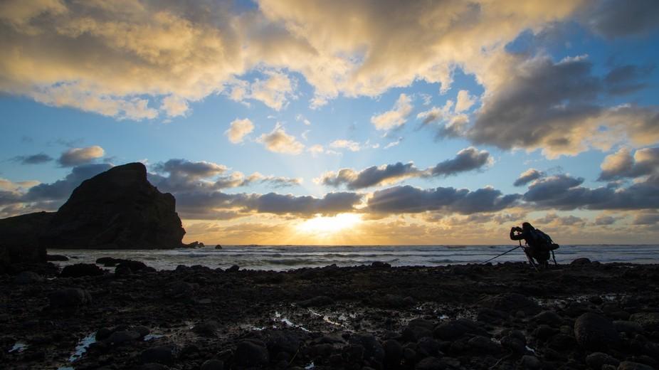 Another photographer lines up the stunning sunset at Piha, NZ.