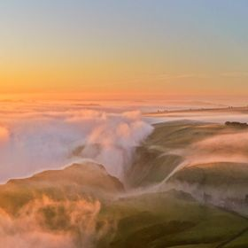 Sunrise from Mam Tor, in the Derbyshire Peak District, UK, with the light shining across the fog bank in the valley below.