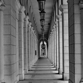 The rows of pillars emphasize the distance from the unknown person at the far end.