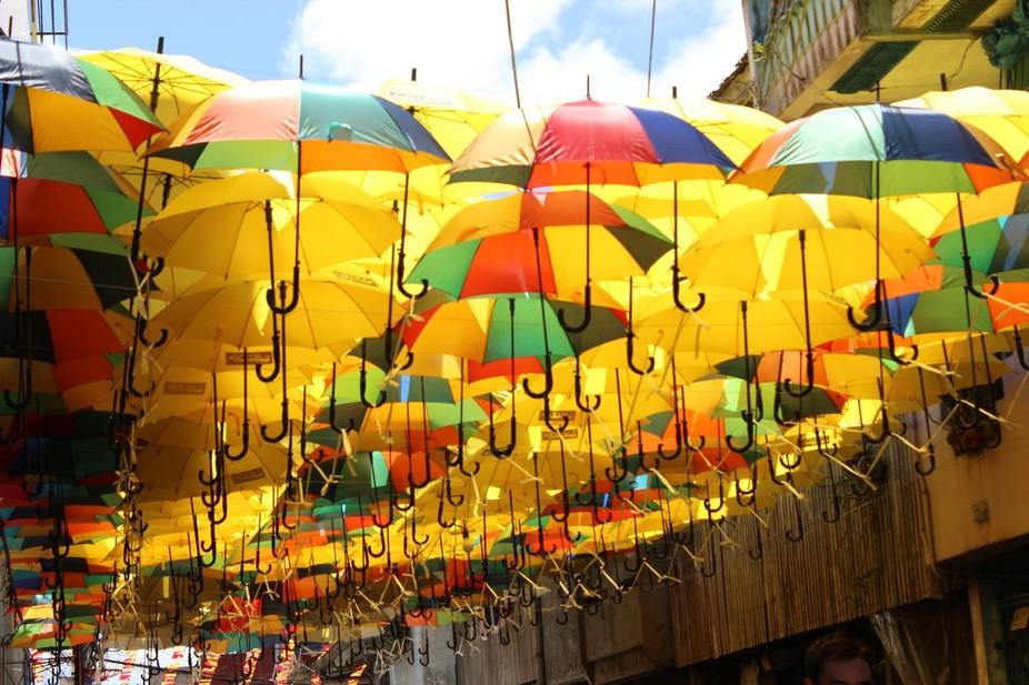 Umbrellas are lined and hooked side by side to give shade to tourists enjoying the Pahiyas Festiv...