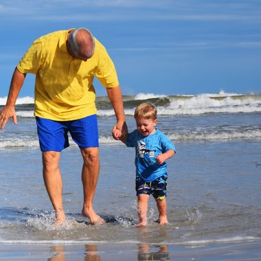 nico and papaw holding hands at beach