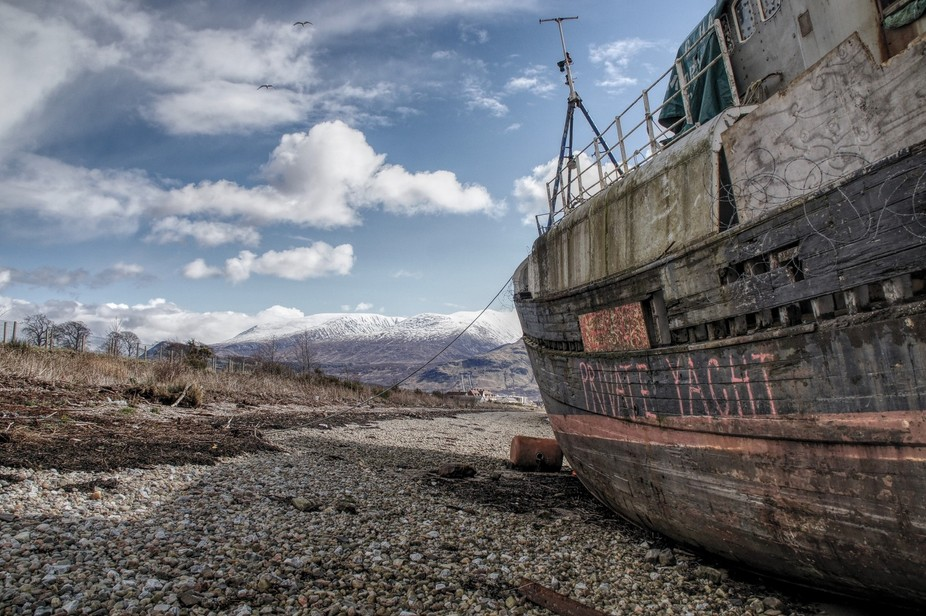 old boat on the shore of loch linnie in Carpach Fort William Scotland with Ben nevis in the backg...