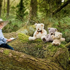 A young boy reads a story to his Teddy Bears out in the woods.