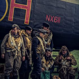 Aircrew in front of their Lancaster bomber waiting for their mission to start. Group of re-enactors at an airshow in the UK.