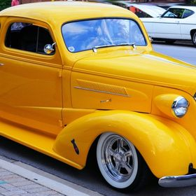 A beautiful Bright yellow antique car showing off its color and emblem.
