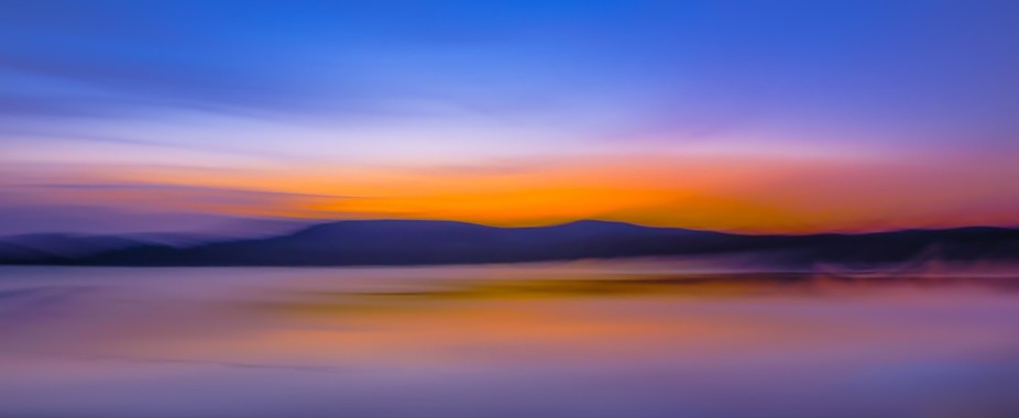 Abstract skyscape at sunset, viewing mountains across water, intentionally blurry and grainy to f...