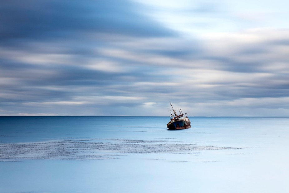 an old fishing boat in punto arenas in chile, lies rusting in the water, waiting to sink to the b...