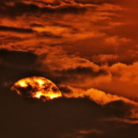 Sun is hidding behind the clouds during golden hours of sunset. Due to orange warm light clouds get beautiful contrast.