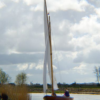 Yacht sailing on the Norfolk Broads, UK, with windmills in the background.