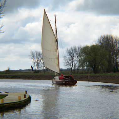 Yacht sailing on the Norfolk Broads on the River Ant in the UK.