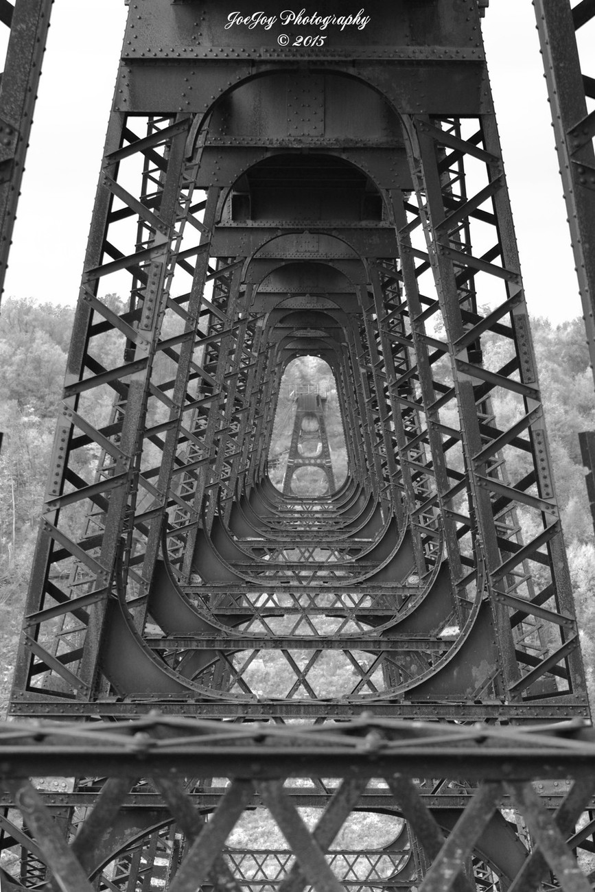 Taken with Nikon D5100 using AF-S Nikkor 70-300 mm 1:4.5-5.6 G lens. Straightened, resized, and converted to black and white using Photoshop Elements 14. This bridge was originally constructed in 1882 by 125 men in just 94 days. In 2003 a tornado knocked down a section of the bridge.