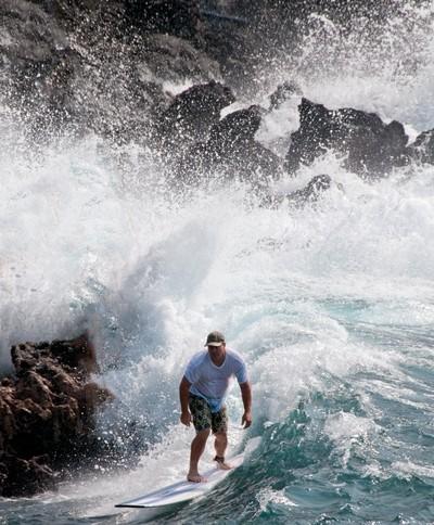 SURFING NEAR THE ROCKS