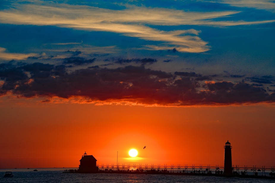 A sunset in Grand Haven Michigan with the old lighthouse