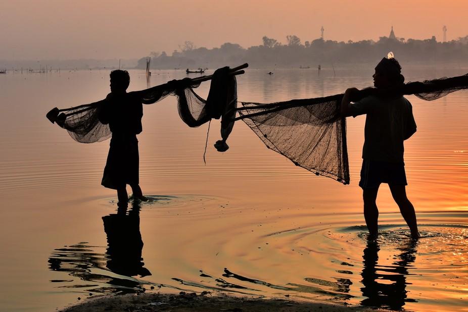 Silhouette of a man casting catch the sunrise at Amarapura,,Mandalay, Myanmar.(U Bein Bridge)