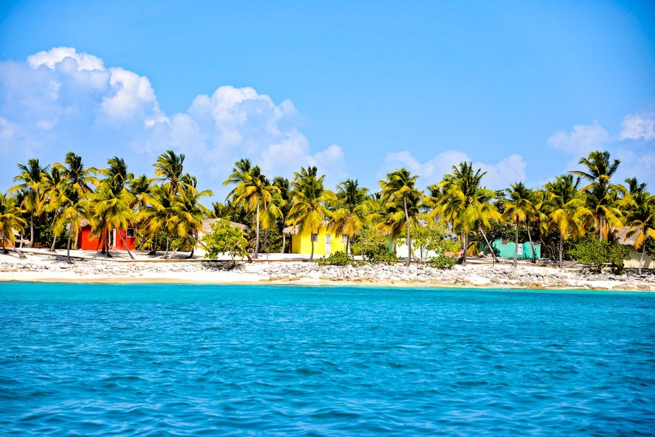 On an island called Catalina in the Dominican Republic, beach huts sit pastel in the sun.